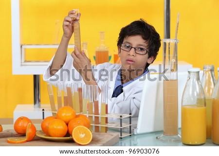 Little boy conducting experiment on orange juice - stock photo
