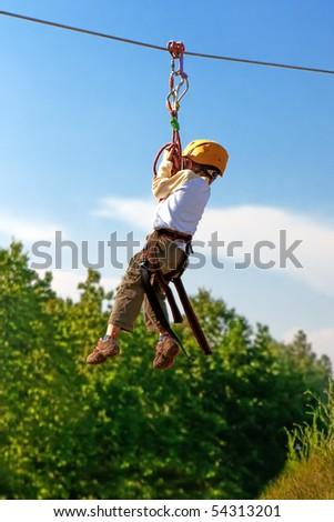 Little boy crossing ravine on rope with alpine equipment - stock photo