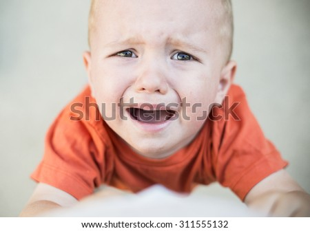 Little boy crying and looking up at the camera - stock photo