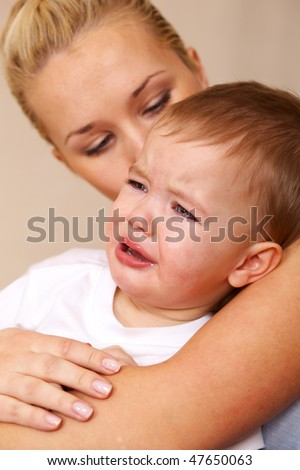 little boy crying in mothers arms - stock photo