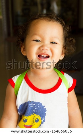 Little boy curly hair with a backpack ready to go to school - stock photo