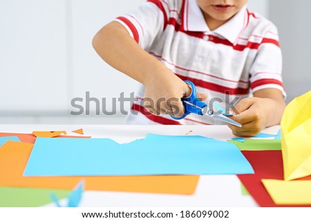 Little boy cutting paper for some craftwork - stock photo