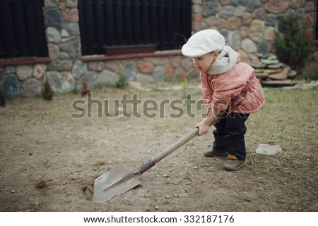 little boy digging a hole in the yard