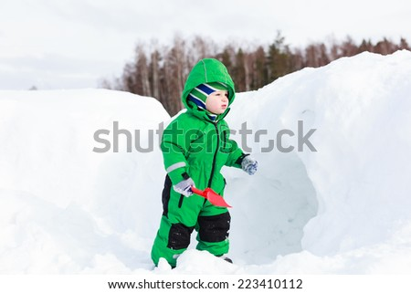 little boy digging winter snow, winter fun - stock photo