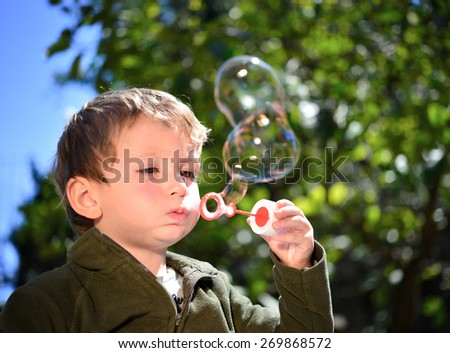 Little boy doing bubble soap outside in a park.
