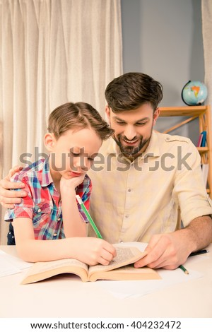 Little boy doing hometask and writing in book with his father - stock photo