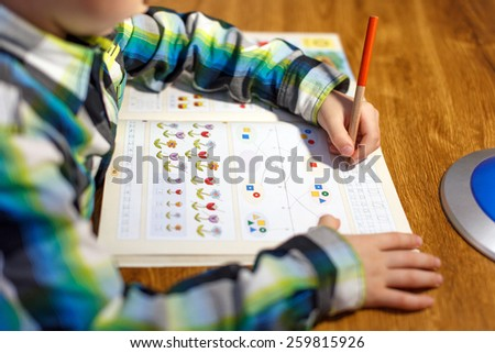 Little boy doing homework at home with pencil into maths workbook - stock photo