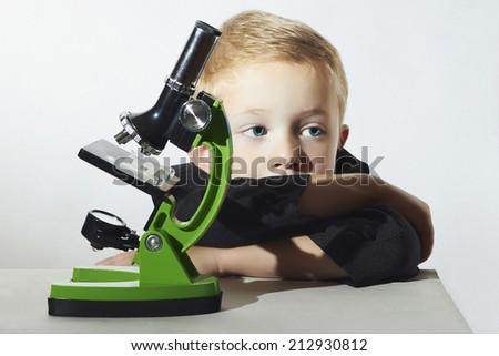 little boy don't want to study.sad child.children.Schoolboy with a microscope.Smart boy.Education - stock photo