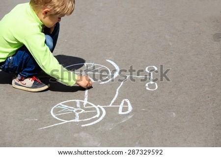 little boy drawing bike on asphalt, kids outdoor activities - stock photo