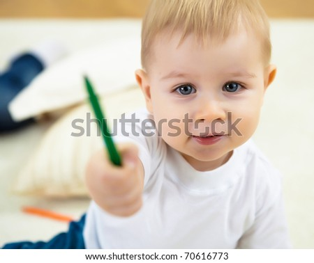 little boy drawing with color pencil and sitting on the floor at home - stock photo