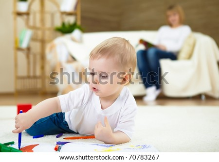 little boy drawing with color pencil and sitting on the floor at home