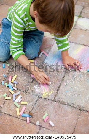 Little boy drawing with colorful chalk and sitting on the pavement - stock photo