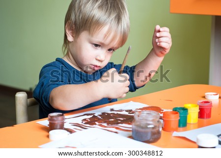 Little boy draws a brush and paint in the nursery