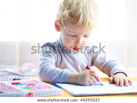 Little boy draws a colored pencil sitting at a table looking at the child a sheet of paper