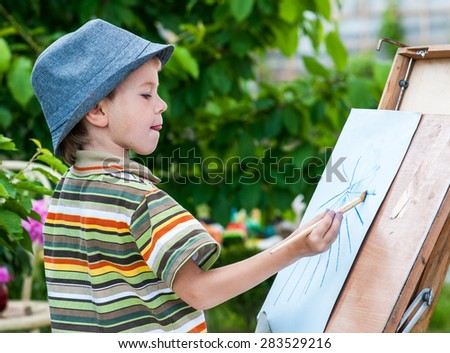 Little boy draws a picture outdoor - stock photo