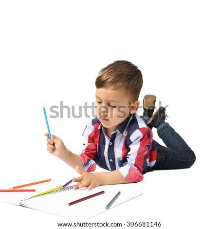 Little boy draws lying on floor isolated on white background