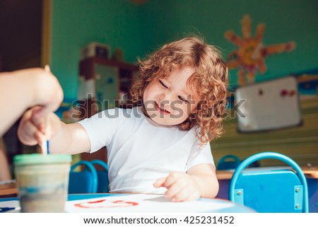 Little boy draws on watercolor paper - stock photo