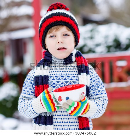 Little boy drinking chocolate drink with marshmallows, outdoors with snow background. Kid boy in winter sweater, hat, long warm scarf and colorfull gloves. On cold snowy winter day. - stock photo