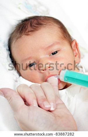 little boy drinking milk from the mother of the syringe