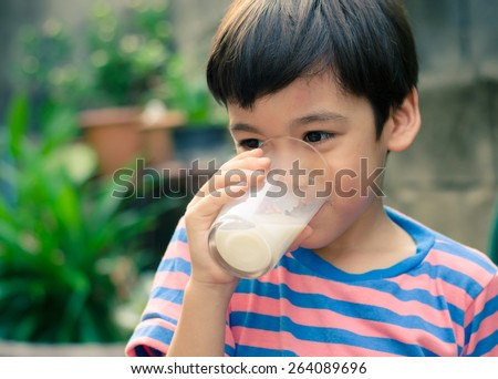 Little boy drinking milk in the park vintage color style - stock photo