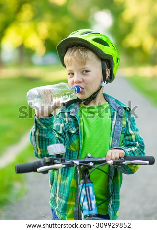 Little boy drinking water by the bike. - stock photo