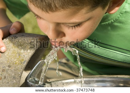 Little boy drinking water from a fountain - stock photo