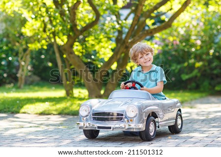 Little boy driving big toy car and having fun, outdoors. - stock photo