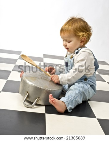 little boy druming playing with pots