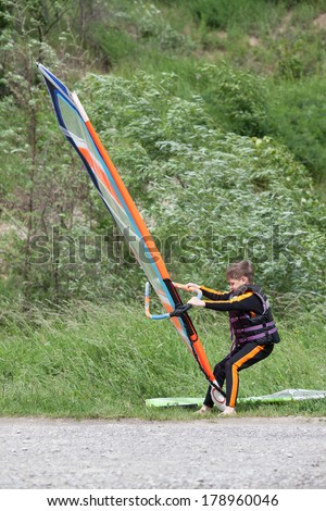 Little boy during windsurfing-lesson in sunny day - stock photo