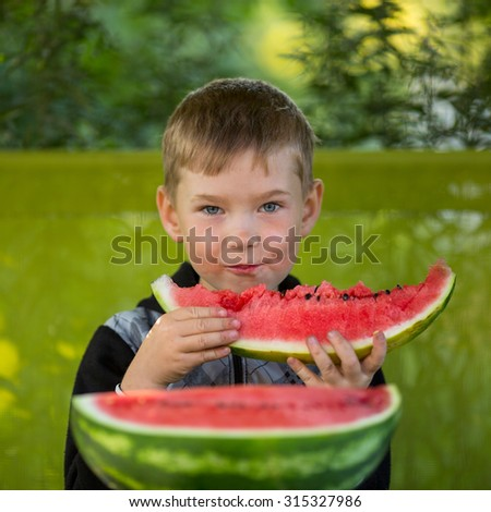 Little boy eating a large watermelon. - stock photo