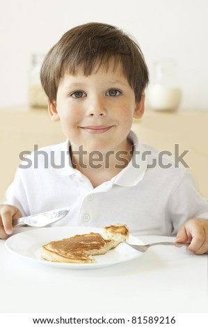 Little boy eating a pancake - stock photo