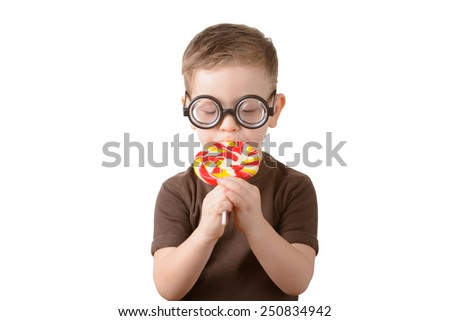 Little boy eating a piece of candy in glasses on a white background - stock photo