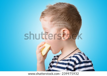 little boy eating an apple on a blue background closeup - stock photo