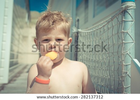 Little boy eating an ice-cream at the beach-house - stock photo