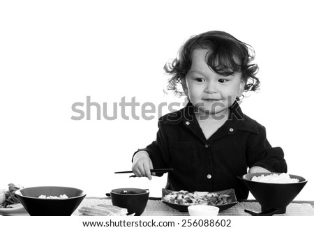 Little boy eating asian food, isolated on a white background. - stock photo