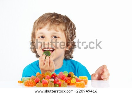 Little boy eating candies on a white background