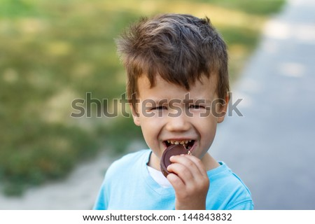 Little boy eating chocolate, outdoor - stock photo