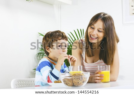 Little boy eating cookies and drinking orange juice with her mum. / Mother and son having breakfast. - stock photo