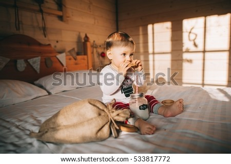 little boy eating cookies in bed