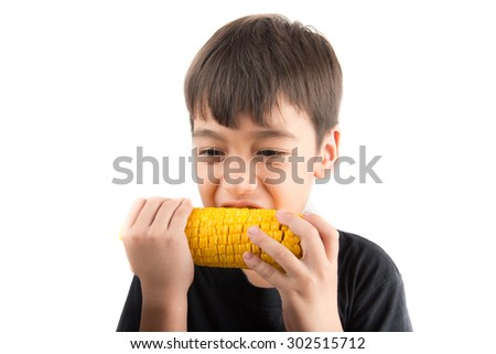 Little boy eating corn on white background - stock photo