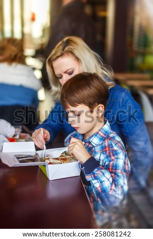 Little boy eating salad with mother in fast food restaurant behind glass - stock photo