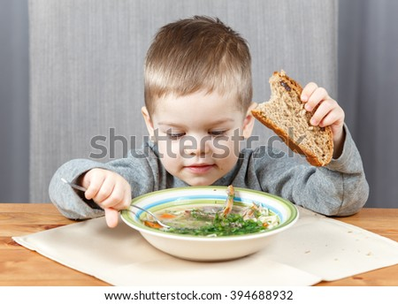 Little boy eating soup for dinner