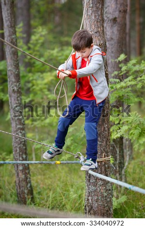 Little boy enjoying activity in the park. Cute little child having fun outdoors climbing on playground - stock photo