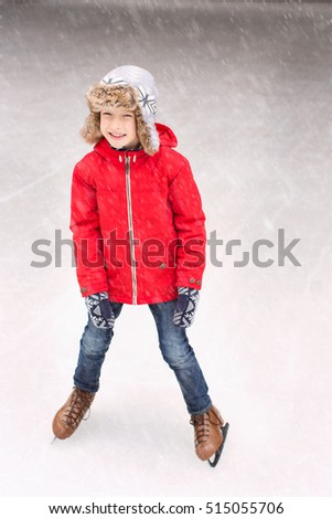little boy enjoying ice skating at winter at outdoor skating rink at snowy weather, winter concept