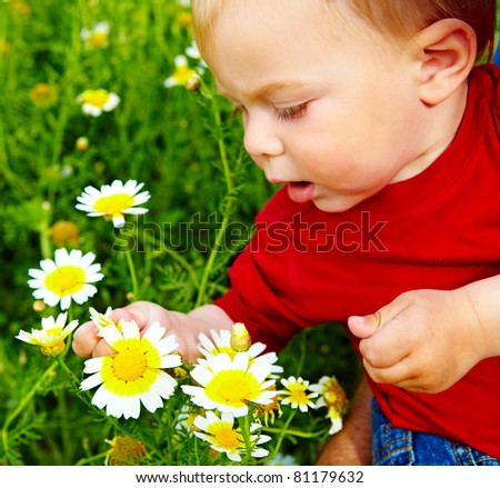 little boy enjoying outdoors in field of flowers on a summer day - stock photo