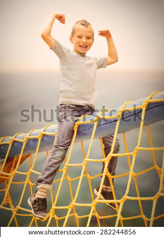 Little boy enjoying summer holidays on the sea. Retro style and warm filtered picture. - stock photo