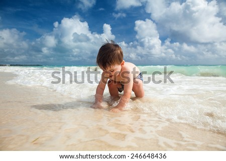 Little boy enjoys summer day at the tropical beach. - stock photo