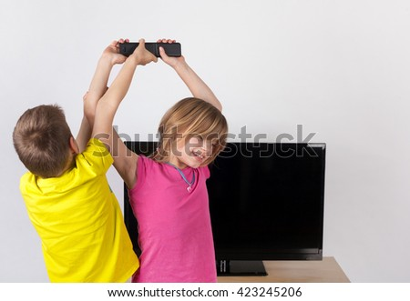 Little boy fighting with his sister for the remote control in front of the TV