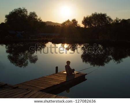 little boy fishing at sunset - stock photo