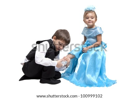 Little boy fitting a glass slipper onto a little girl - stock photo